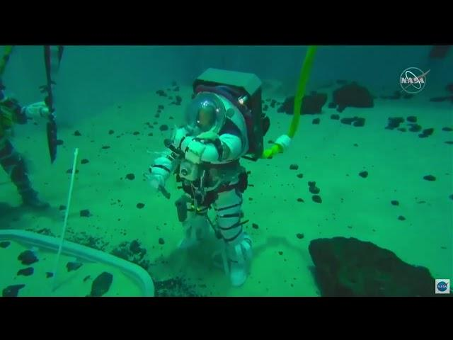 NASA astronauts test new spacesuit in pool, plant flag
